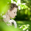 Woman with a hair braid in a blossoming park. — Stockfoto