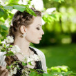 Woman with a hair braid in a blossoming park. — Stock Photo