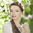 Woman with a hair braid in a blossoming park. — Стоковая фотография