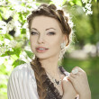 Woman with a hair braid in a blossoming park. — Foto Stock
