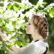 Woman with a hair braid in a blossoming park. - Stock Photo