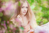 Beautiful woman with flowering tree — Stock Photo