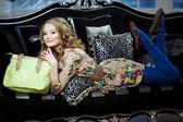 γυναίκα ομορφιά σε πολυτελή καναπέ με τσάντα — Φωτογραφία Αρχείου
