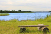 Wooden bench by the lake — Stock Photo