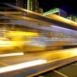 High speed and blurred bus light trails in downtown nightscape — Stock Photo #10739315