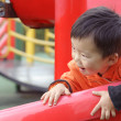 Stock Photo: Baby playing on sliding board