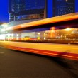 High speed and blurred bus light trails in downtown nightscape — Stock Photo