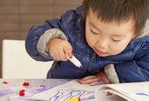 En söt baby är målning på bordet — Stockfoto