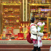 A mother holding a child to look in the window of a gold shop — Stock Photo