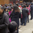 Stock Photo: Crowded waiting in line to enter temple to pray to Buddha