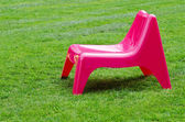 Pink chair on green grass — Stock Photo