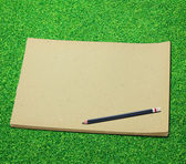 Pencil and old blank sketch book on green grass background — Zdjęcie stockowe