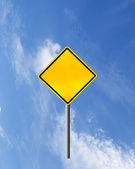 Blank yellow road warning sign on sky — Zdjęcie stockowe