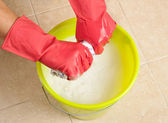 Hands in red rubber gloves wringing the water out of a mop cloth — Stock Photo