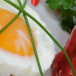 Fried Eggs Sunny Side Up with greens and bacon - Stock Photo