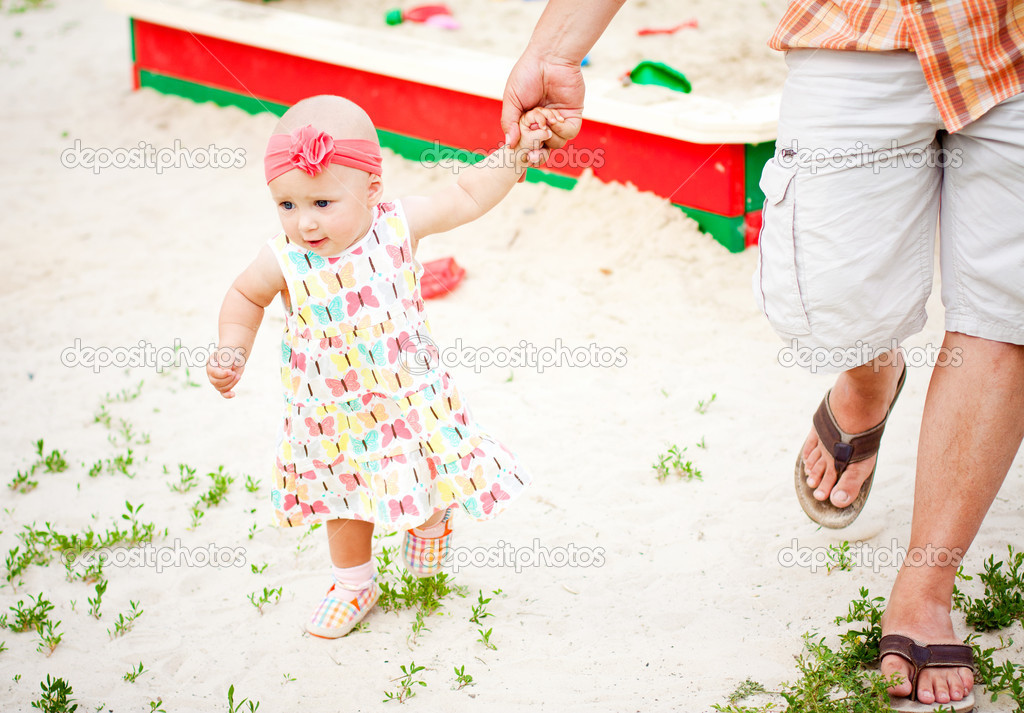 Baby girl first steps holding her father hand — Stock Photo #11391827