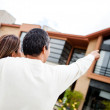 Couple pointing at their dream home - Stock Photo