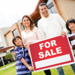 Family with house for sale - Stock Photo