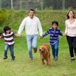Royalty-Free Stock Photo: Family chasing a dog