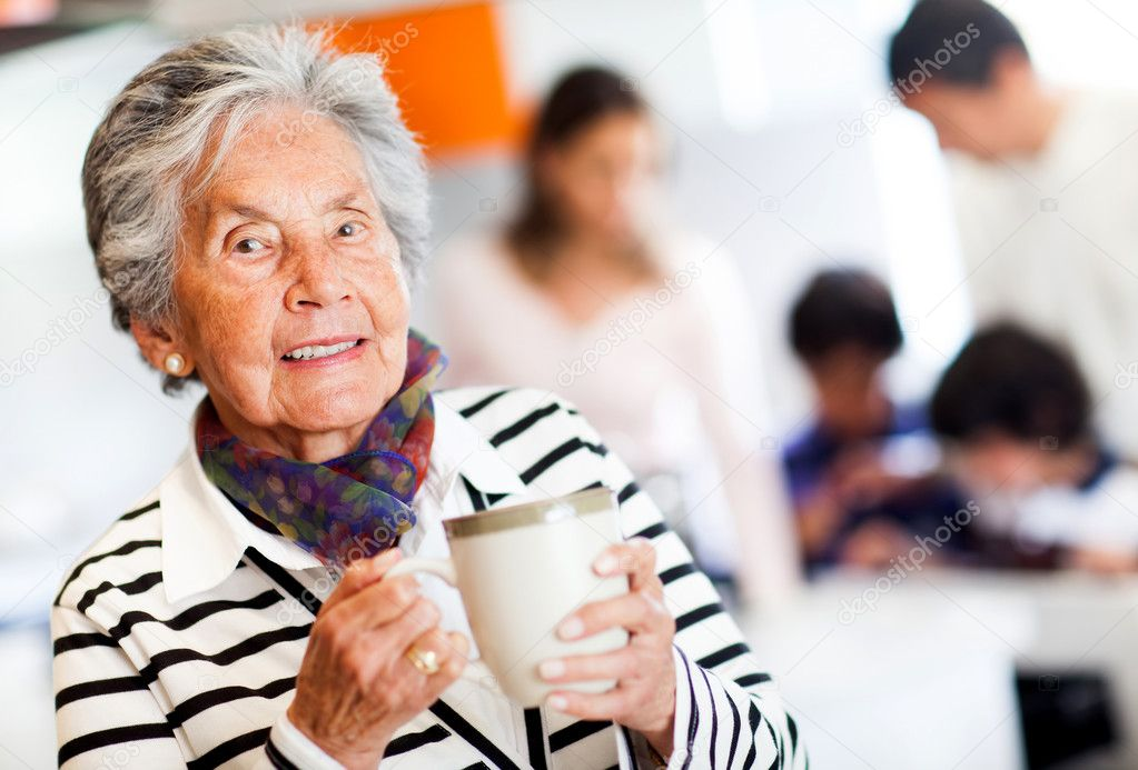 Old woman holding a cup of tea and smiling — Stock Photo #11029924