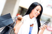 Shopping woman sending a text — Stockfoto
