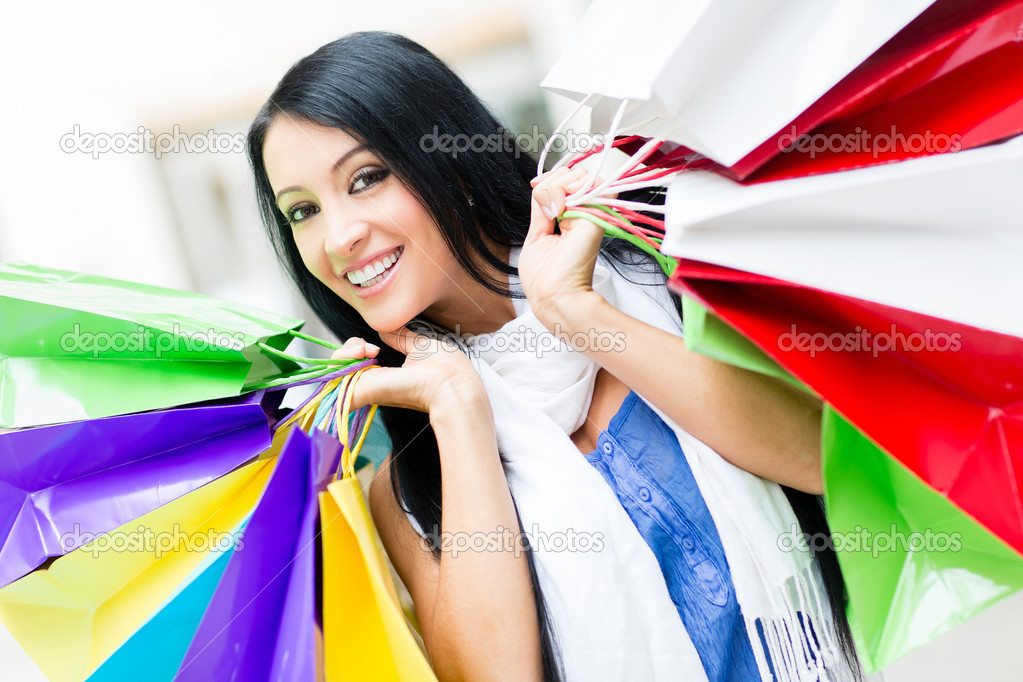 Portrait of a compulsive buyer holding shopping bags — Stock Photo #11045733