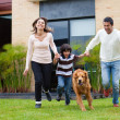 Family chasing a dog — Stock Photo