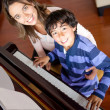 Boy learning to play piano - Stock fotografie