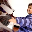 Boy excited about piano lessons - Stock Photo
