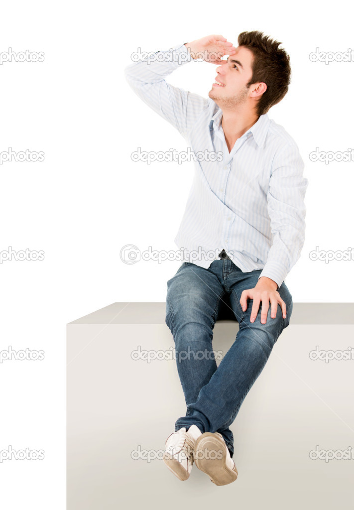 Man sitting on a cube and looking away - isolated over white  Stock Photo #11252109