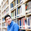 Thoughtful student at the library - Stock Photo