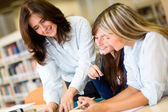 Female students at the library — Stock Photo
