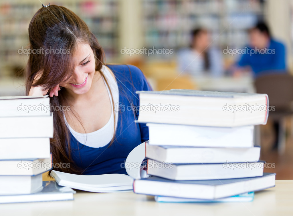Student reading at the library with a pile of books — Stock Photo #11293621