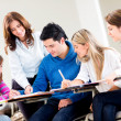 Stock Photo: Teacher helping some students