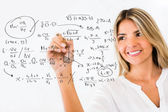 Female student writing formulas — Stock Photo