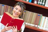 Dívka čtení v knihovně — Stock fotografie