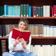 Woman reading at the library — Stock Photo