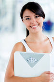 Fit woman with a scale — Stock Photo