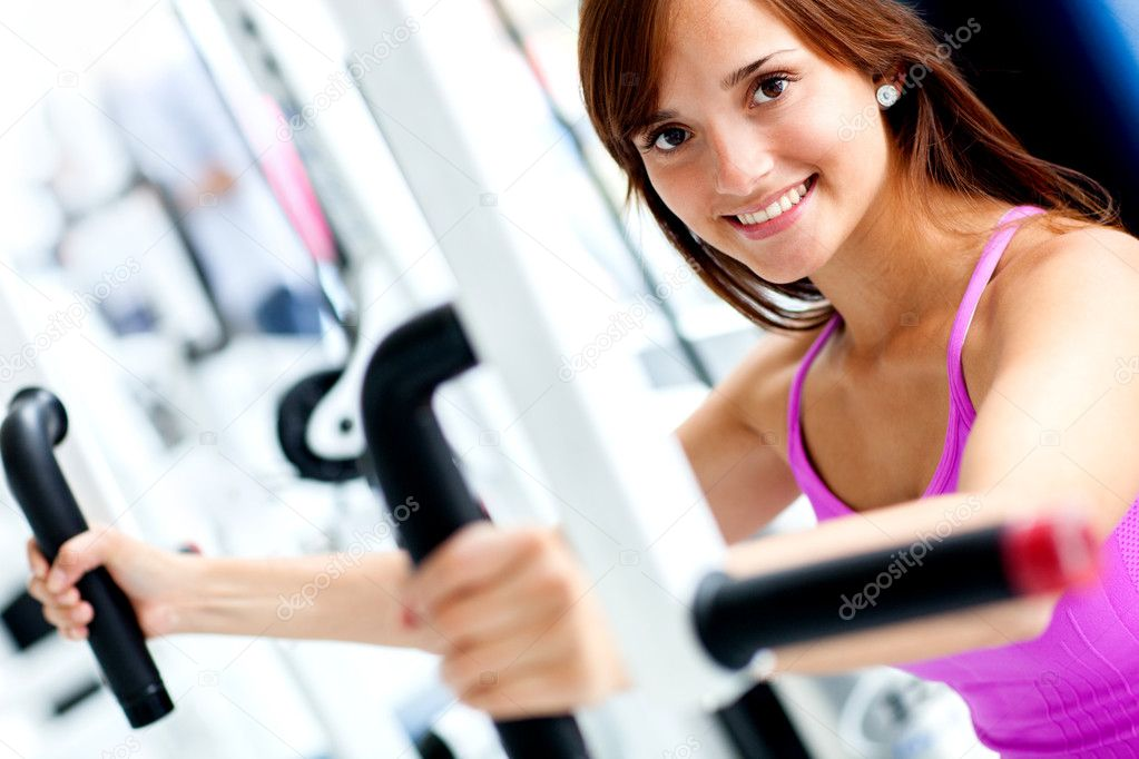 Beautiful woman exercising at the gym on a machine — Stock Photo #11747890