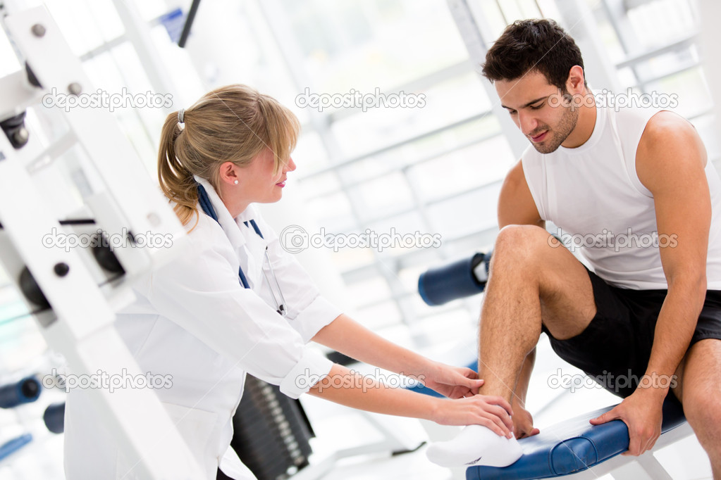 Injured man at the gym feeling pain in his ankle  Stock Photo #11848556
