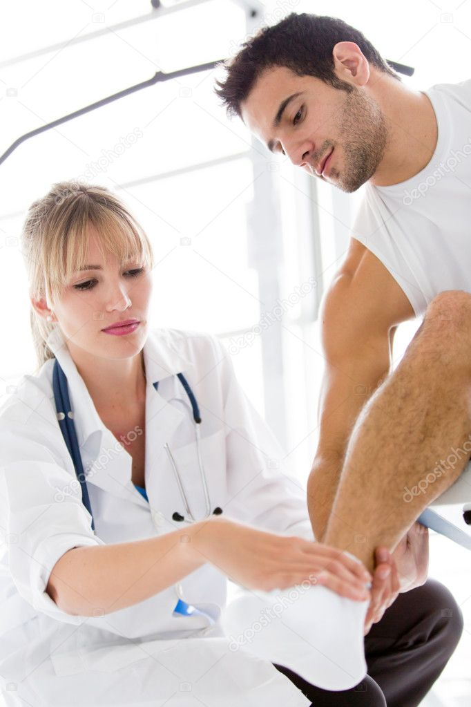 Athletic man with an injury in his ankle being checked by a doctor — Stock Photo #11848564