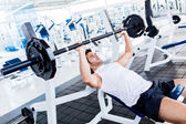 Gym man lifting weights — Stockfoto