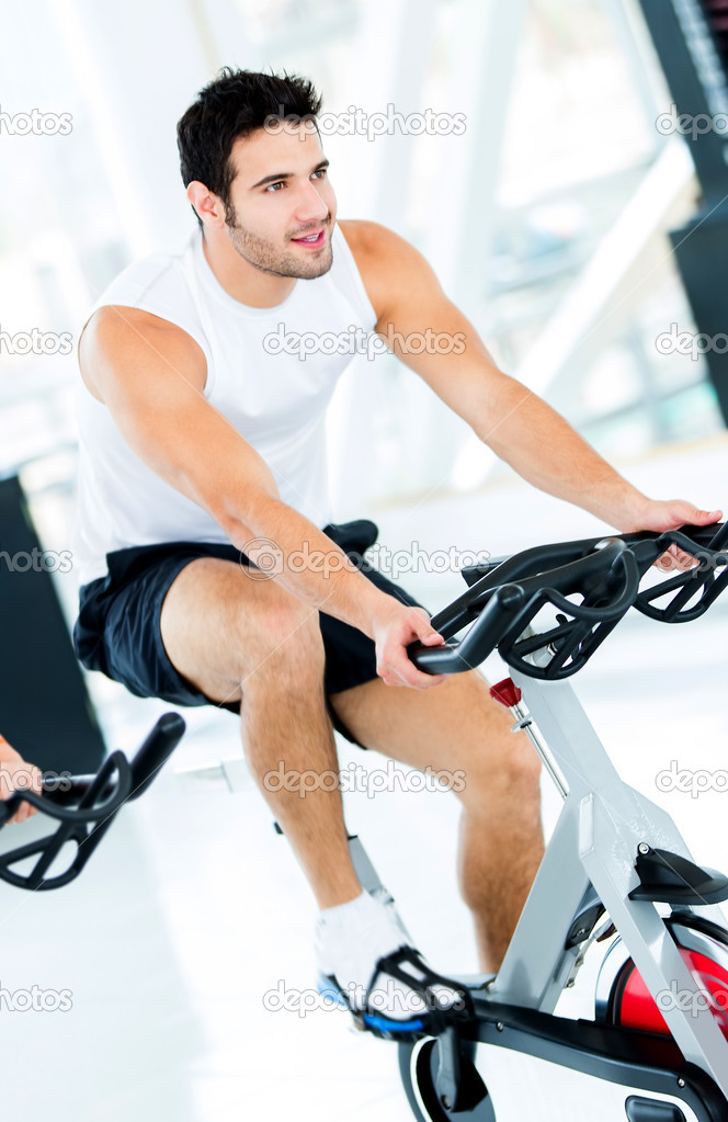 Handsome man doing spinning at the gym — Stock Photo #12007253