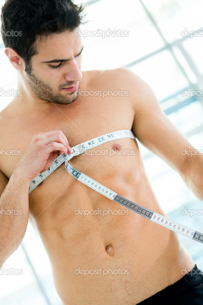 Fit man measuring his muscles at the gym  Stock Photo #12007275