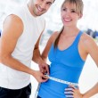 Personal trainer measuring a woman — Stock Photo #12046218