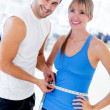 Stock Photo: Personal trainer measuring woman