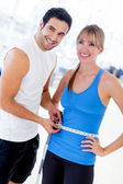Personal trainer measuring a woman — Foto Stock