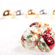 Christmas baubles on snow with gold and silver baubles in a line — Stock Photo