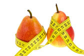 Two pears with tape measure on waistes. — Stock Photo