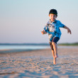 Kid Runs On The Beach at sunset — Stock Photo #11011744